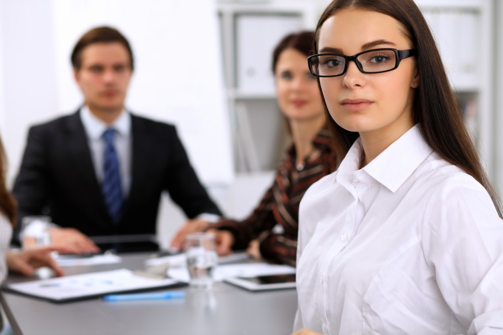 Portrait of a young business woman against a group of business people at a meeting.
